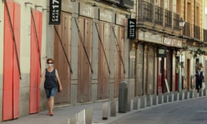 A woman walks past closed restaurants in Madrid