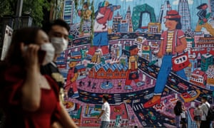 People wearing protective face masks walk by a giant painting depicting the capital city amid coronavirus pandemic at 798 art zone in Beijing, China, 26 June 2020.