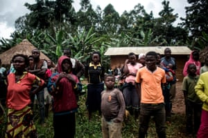 A group of Congolese people look on as the corpse of a suspected Ebola victim is picked up, in North Kivu province