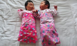 Two newborn babies lie on a hospital bed in Beijing