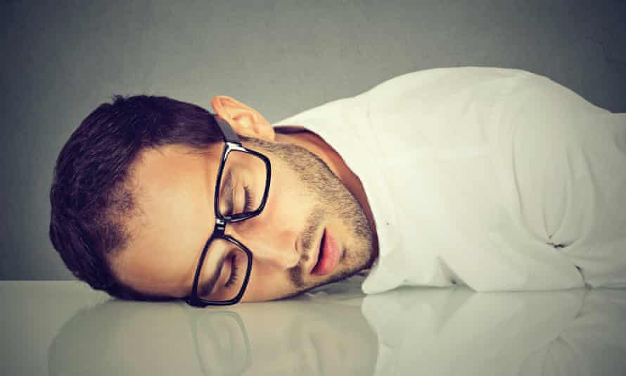 A man with glasses sleeping on a desk