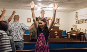 young woman raises hands in church