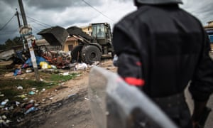 Gabonese police officers secure the perimeter, as a military bulldozer clears a barricade.