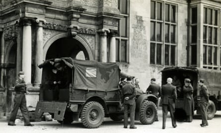 soldiers in uniform gather around two army vehicles