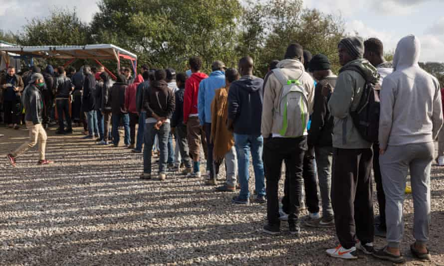 Refugees queue for food at the camp in Calais