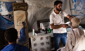 Displaced Syrians who fled the fighting in Raqqa and Deir al Zour seen inside a tent that serves as a barber shop in the Ain Issa IDP camp.
