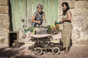 A woman sells capers and other delicacies from her old pram on the streets of Marsaxlokk, a fishing village in Malta.