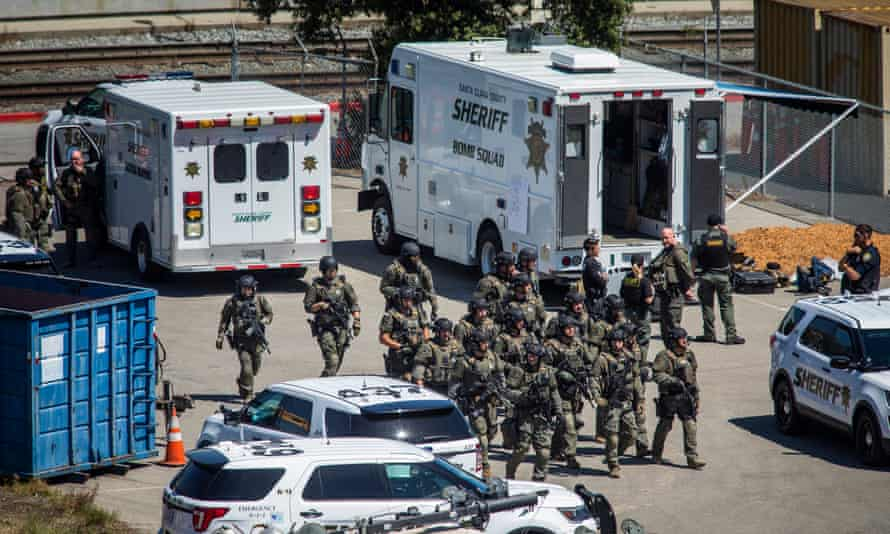 Tactical law enforcement officers move through the light-rail yard in San Jose, California, on Wednesday where a mass shooting left 10 people dead, including the gunman.