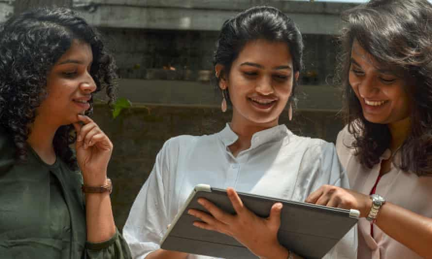Three young smiling women working outdoors on mobile device