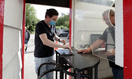 A football spectator buying a ticket at a screened turnstile