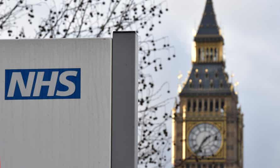 A National Health Service logo is seen on a hospital sign in front of the Big Ben clock tower of the Houses of Parliament, in central London