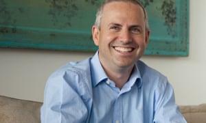 Tim Steiner smiles sitting in blue shirt on a sofa