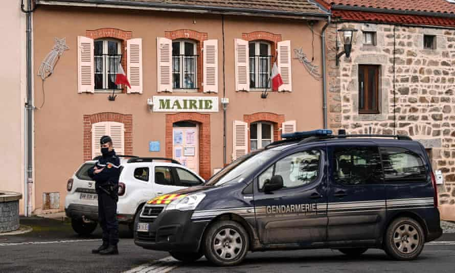 A gendarme stands in front of the town hall in Saint-Just after three officers were killed.