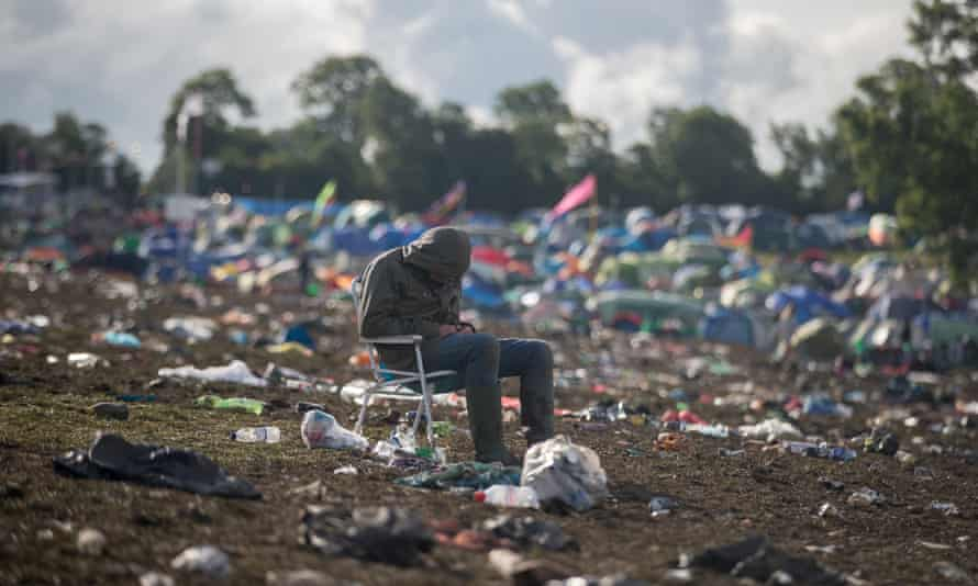 A man sits in a chair left behind as the clear up begins at the Glastonbury festival 2016