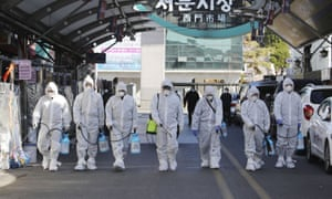 Workers wearing protective gears spray disinfectant at a local market in Daegu, South Korea.