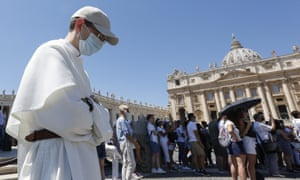A friar wearing a protective mask prays during the Angelus prayer celebrated by Pope Francis from his studio window overlooking St Peter's Square