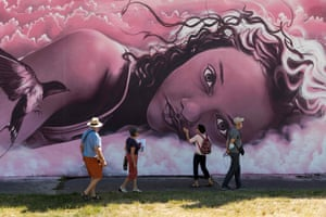 Lurcy-Levis, France: Tourists admire a mural during a visit to Street Art City