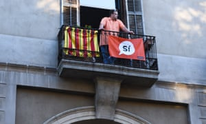 Man on balcony with Spanish and 'Si' flags