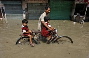 A man transports his daughters home from school  through a flooded road in Kolkata