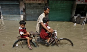 A man takes his daughters home from school on a bicycle through a flooded road in Kolkata.