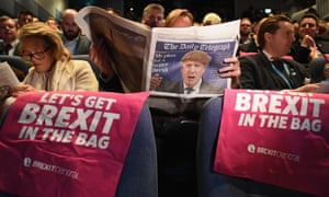 A delegate reads The Daily Telegraph as they attend the Conservative party conference