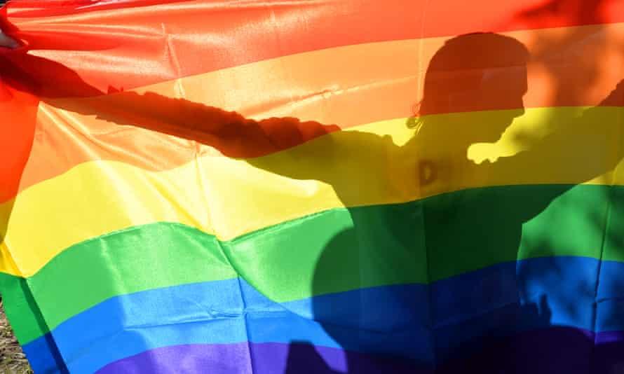 An activist's silhouette behind a rainbow gay pride flag