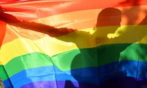 A gay activist holds up a rainbow flag …