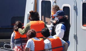 A Border Force officer escorts a young family thought to be migrants from a Border Force vessel after they were brought into Dover, Kent.