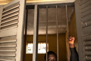Patient looks out of a caged window at Accra Psychiatric Hospital