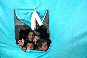Boys look out of a tent used as a classroom for displaced children, at a camp for displaced families from al-Bayada city, Syria