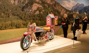 Visitors admire Grayson Perry's pink motorbike teddy bear pilgrimage at the Arnolfini