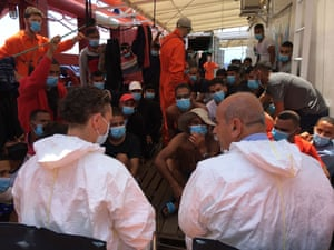 People rescued at sea sit on the deck of the 'Ocean Viking' rescue ship, jointly operated by French NGOs SOS Mediterranee and Medecins sans Frontieres (MSF Doctors without Borders) in the Mediterranean Sea on 4 July, 2020.