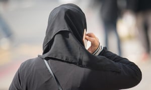A Muslim woman wearing a hijab talks on her mobile phone.