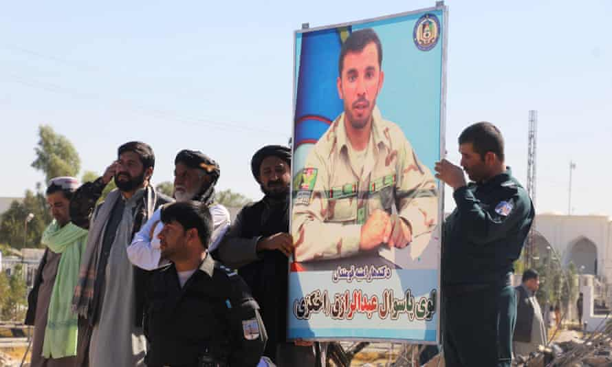 Afghan officials attend the burial of police chief Abdul Raziq, in Kandahar.