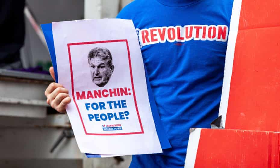 An activist holds a flyer questioning Senator Joe Manchin on Capitol Hill on Tuesday.