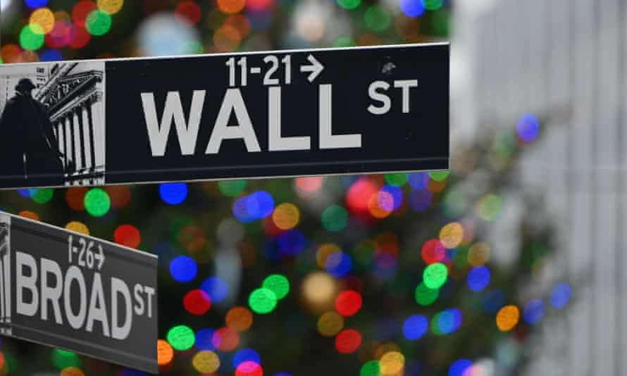 the Wall Street sign at the New York Stock Exchange with Christmas tree lights in the background