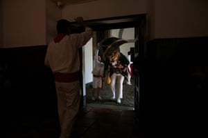 A Kiliki bends over to get through a door during San Fermin festival's Comparsa de gigantes y cabezudos (Parade of the Giants and Big Heads) in Pamplona