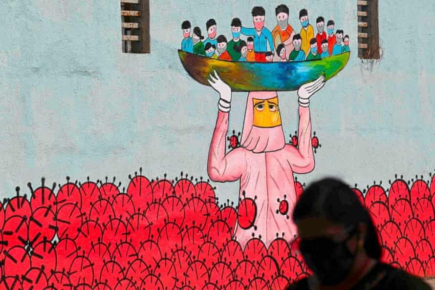 A pedestrian walks past a wall mural depicting a mother saving children from a sea of coronavirus, in Mumbai, India.