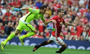 Manchester United's Henrikh Mkhitaryan takes to the turf as he tussles with Manchester City's Claudio Bravo.