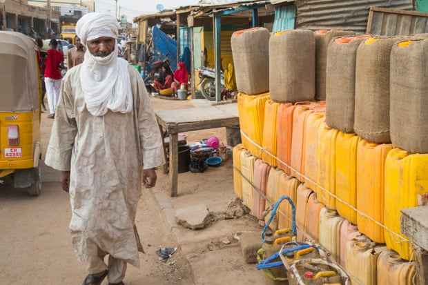A man walks past water cans in Agadez market