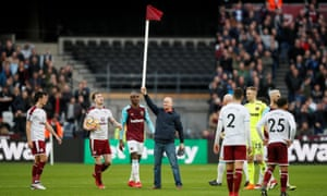 A West Ham fan holds up a corner flag after invading the pitch during the game against Burnley.