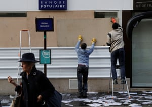 Workers board up the broken window of a bank