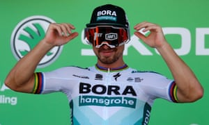 Peter Sagan celebrates his race win on the podium, before receiving the green jersey for the race's leading sprinter.