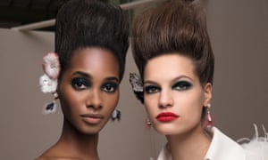 A black and a white model side by side, both with heavily made up eyes and lips