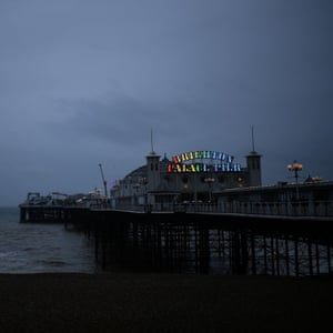 The Brighton Palace Pier sign is illuminated with rainbow colours