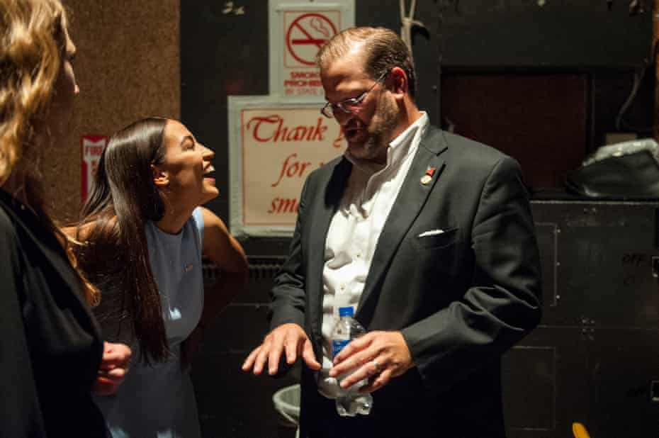 Alexandria Ocasio-Cortez laughs backstage with congressional candidate James Thompson.