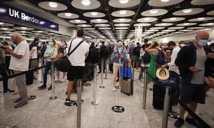 Arriving passengers queue at Heathrow airport in June.
