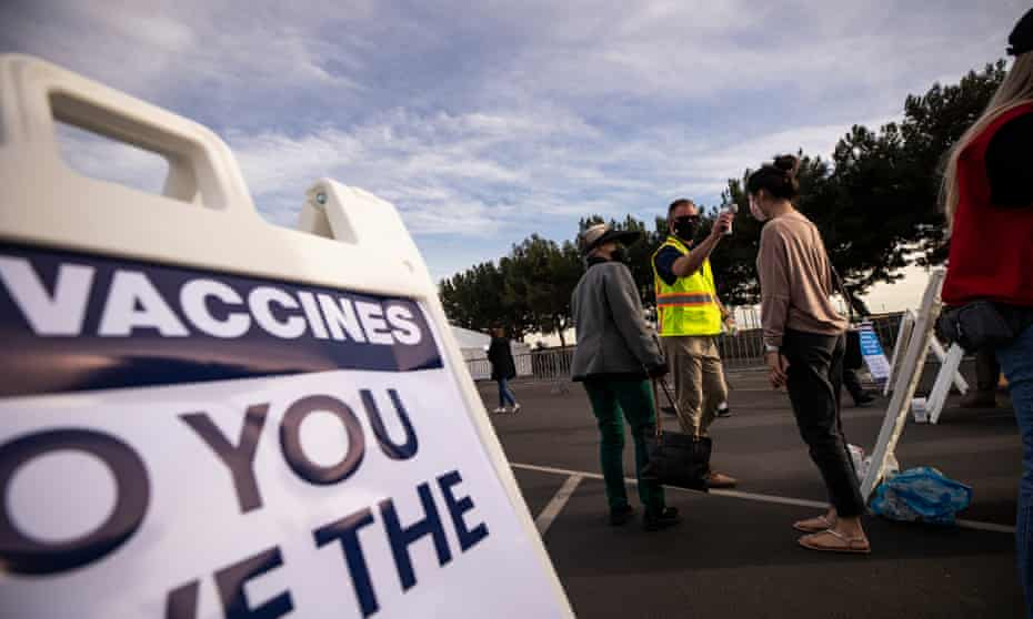 People queue as they wait to get vaccinated against Covid-19 in a parking lot at Disneyland in Anaheim, California, this week.
