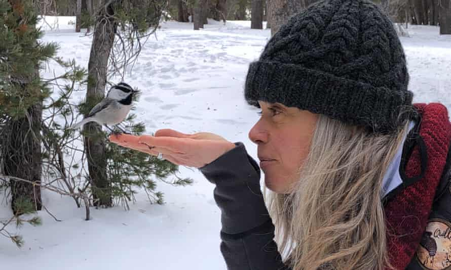 Woniya Thibeault with a chickadee on her hand.
