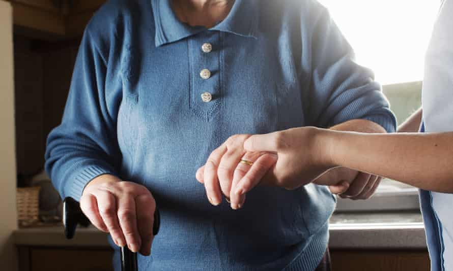 A personal care assistant helps an older woman to walk.